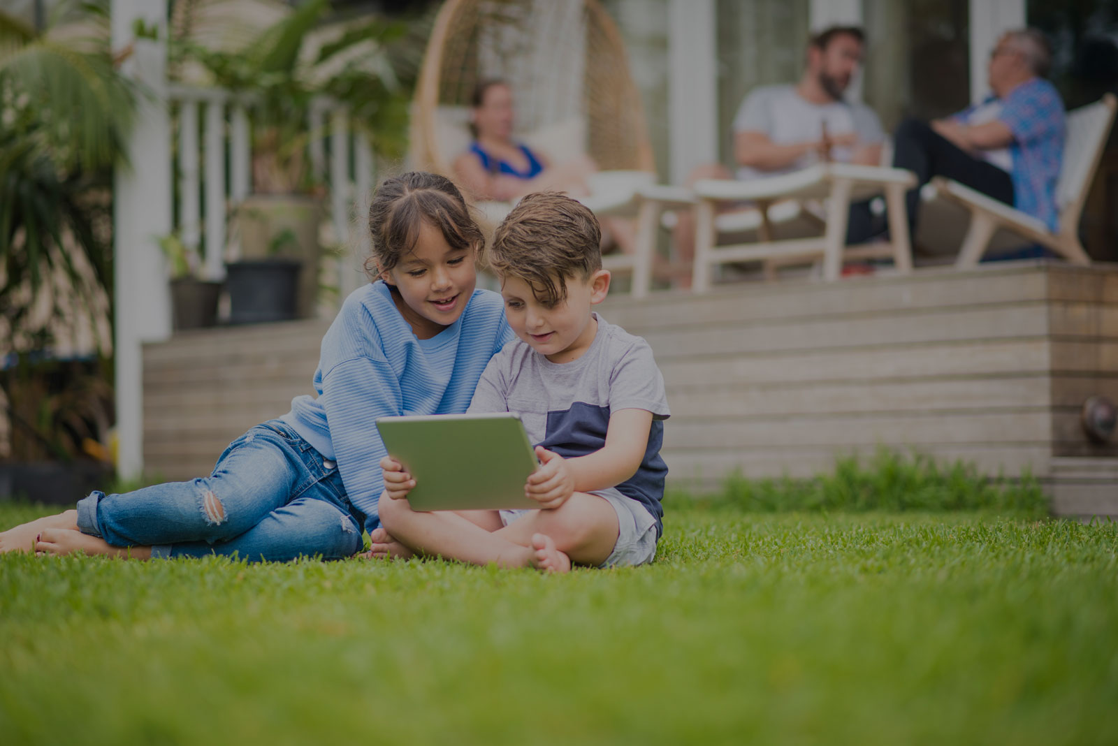 two children looking at a tablet tint